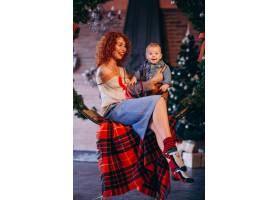 母亲带着她的小儿子在圣诞树旁_3654124