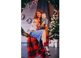 母亲带着她的小儿子在圣诞树旁_3654125