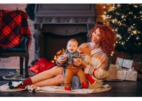 母亲带着她的小儿子在圣诞树旁_3655265