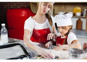 穿着相同衣服的妈妈和女儿在舒适的厨房里准_3342078