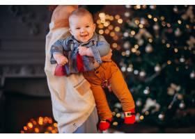 母亲带着她的小儿子在圣诞树旁_3655269