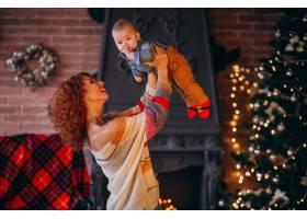 母亲带着她的小儿子在圣诞树旁_3655284