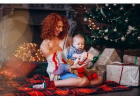 母亲带着她的小儿子在圣诞树旁带着礼物_3655972