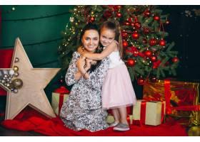 母亲带着她的小女儿在圣诞树旁_3654149