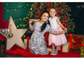 母亲带着她的小女儿在圣诞树旁_3654150