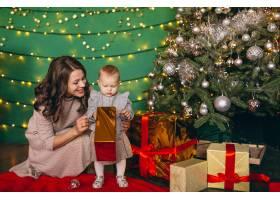 母亲带着她的小女儿在圣诞树旁_3655311