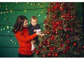 母亲带着她的小女儿在圣诞树旁_3655325