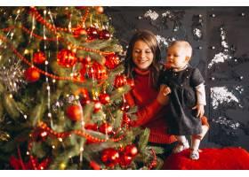 母亲带着她的小女儿在圣诞树旁_3655326
