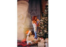 母亲带着孩子装饰圣诞树_3655997