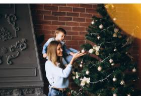 母亲带着小女儿装饰圣诞树_3655469