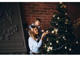 母亲带着小女儿装饰圣诞树_3655470