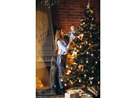 母亲带着小女儿装饰圣诞树_3655476