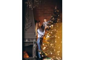 母亲带着小女儿装饰圣诞树_3655477