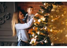 母亲带着小女儿装饰圣诞树_3655478