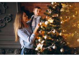 母亲带着小女儿装饰圣诞树_3655479