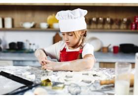 迷人的女孩在舒适的厨房里用面团做饼干很有_3342080