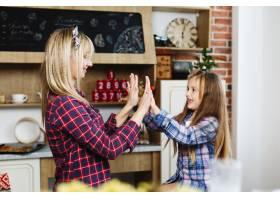 迷人的母女俩在舒适的厨房里玩得开心_3342093