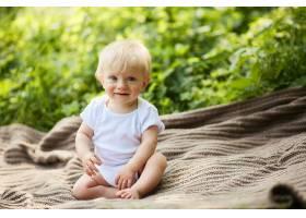 迷人的金发小男孩坐在夏季公园的格子花呢上_3712880