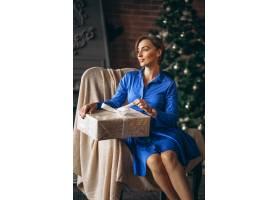 美女在圣誕樹旁拆開禮物_3654194