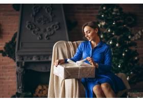 美女在圣誕樹旁拆開禮物_3654195