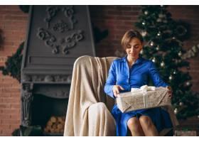 美女在圣誕樹旁拆開禮物_3654196