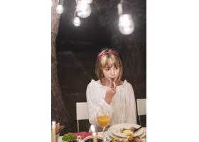 年轻女孩在圣诞晚餐上用叉子吃饭_3479783