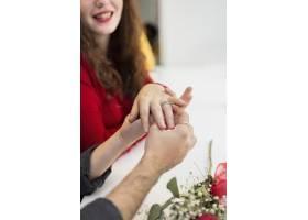 年轻男子把结婚戒指戴在女人的手指上_3597104