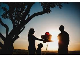 幸福的父母和他们的孩子在树下的绿色草坪上_3711297