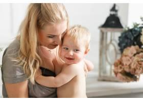 开心地笑着的宝宝和欢快的年轻微笑的母亲拥_3337141