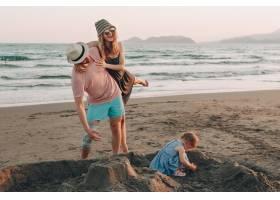 快乐的年轻家庭带着小孩子在海滩上玩得很开_3341305