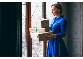拿着圣诞礼物的妇女站在窗边_3655372