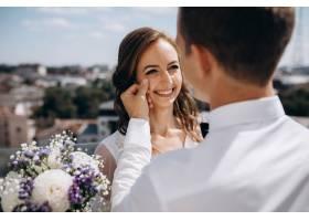 新郎抱着站在屋顶上的新娘周围有美丽的夏_3339436