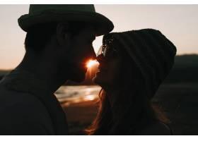 日落海滩背景下浪漫情侣相互凝视的侧写_3341307