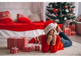 在圣诞树旁拿着圣诞礼物的妇女_3654179