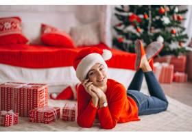 在圣诞树旁拿着圣诞礼物的妇女_3654180