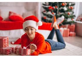 在圣诞树旁拿着圣诞礼物的妇女_3654181