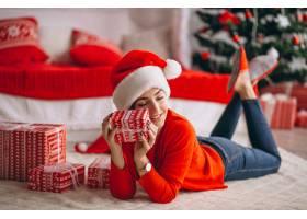 在圣诞树旁拿着圣诞礼物的妇女_3654182
