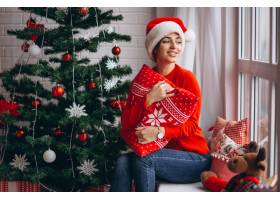 在圣诞树旁拿着圣诞礼物的妇女_3654183