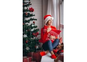 在圣诞树旁拿着圣诞礼物的妇女_3654184