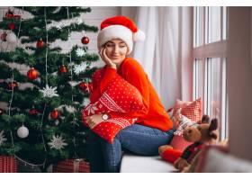 在圣诞树旁拿着圣诞礼物的妇女_3654186