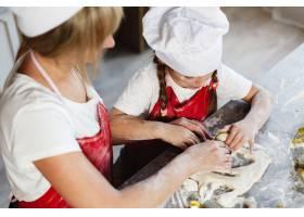 在舒适的厨房里妈妈和女儿在餐桌上用牛奶_3342083