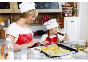 在舒适的厨房里妈妈和女儿在餐桌上用牛奶_3342086