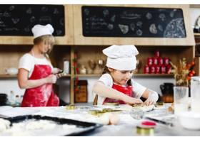 小酋长迷人的女孩在舒适的厨房里用面团做_3342082