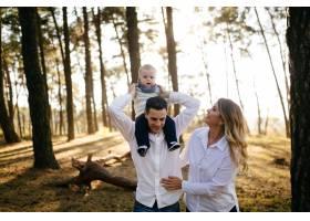 一对年轻夫妇带着一个小男孩走在树林里_3280591