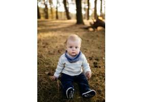 一对年轻夫妇带着一个小男孩走在树林里_3280593