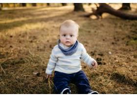 一对年轻夫妇带着一个小男孩走在树林里_3280594
