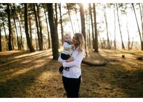 一对年轻夫妇带着一个小男孩走在树林里_3280595