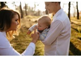 一对年轻夫妇带着一个小男孩走在树林里_3280596