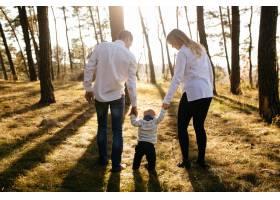 一对年轻夫妇带着一个小男孩走在树林里_3280598