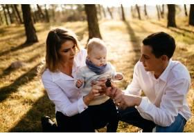 一对年轻夫妇带着一个小男孩走在树林里_3280600